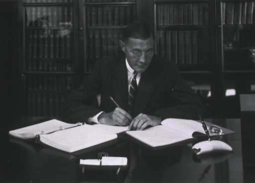 <p>Seated at his desk, half length; writing in notebooks; bookcases in background.</p>
