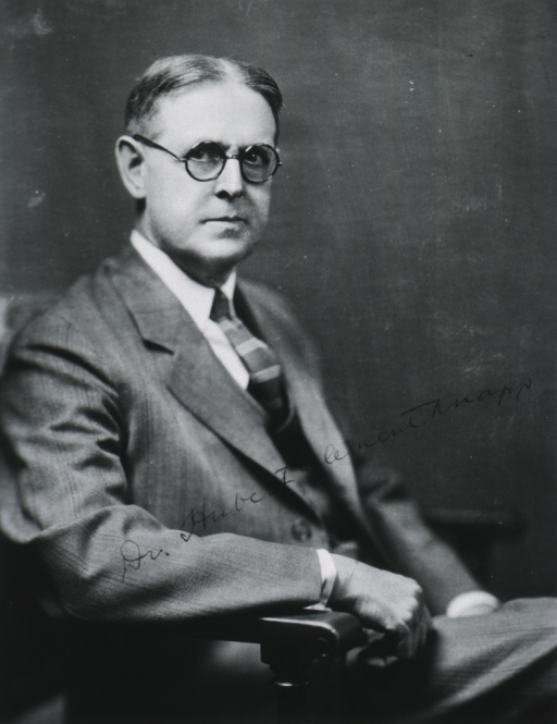 <p>Half-length, seated, right pose, full face; wearing glasses.</p>