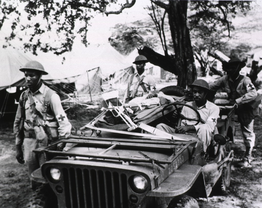 <p>A serviceman sits at the wheel of a jeep.  Next to him on a litter that stretches over the passenger seat lies a wounded soldier.  Three servicemen each stand at a corner of the jeep.  Behind them is a row of tents.</p>