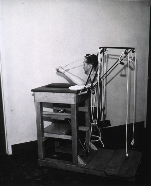 <p>Patient using weight machine for arm exercise (High resistive exercise table).</p>