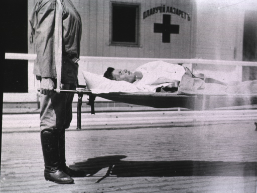 <p>A patient is being carried by two men on a German litter, one of the men is not shown.</p>