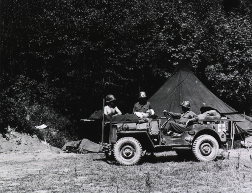 <p>A jeep converted into an ambulance is parked next to a tent.  A serviceman sits at the wheel.  A wounded soldier lies on a litter that is stretched across the hood of the jeep.  Two other servicemen stand next to the wounded soldier.  A forest of trees spreads across the background.  (Cf. no. 34, which is a close-up view of the same subject.)</p>