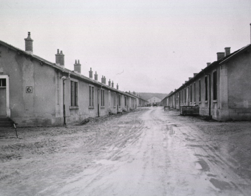 <p>A narrow, muddy road separates two long, one-story buildings.</p>