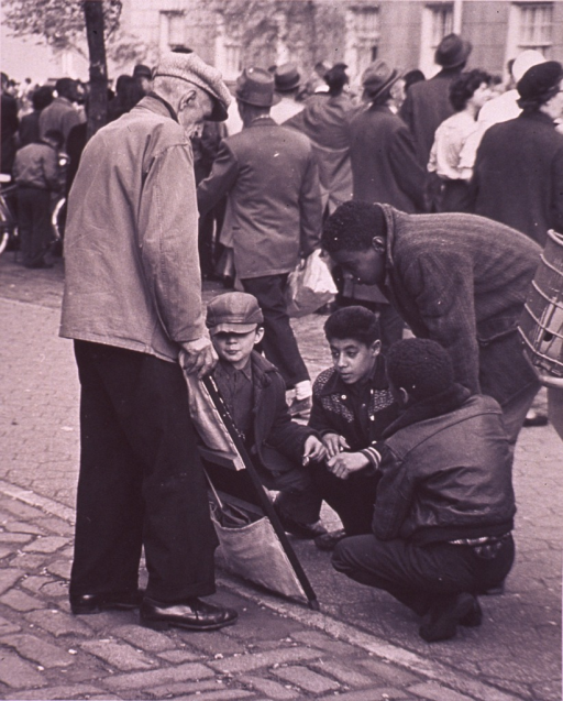 <p>Several boys are looking at a display of items (possibly for sale) held by an old man; a crowd of people in the background is apparently watching a parade.</p>