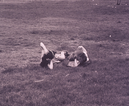 <p>Two girls lying in the grass.</p>