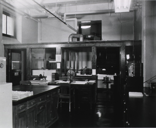 <p>Interior view: two desks, a microscope under glass, counters with drawers and cabinets in the center of the room and against the wall, two partitioned rooms, a ventilation system on the upper back wall, and exposed pipes in the ceiling.</p>