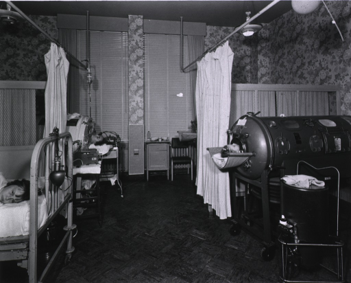 <p>Interior view of hospital unit for poliomyelitis patients; the unit contains three iron lung apparatus, two of which are occupied, and one bed, also occupied.</p>