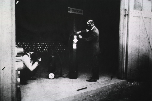 <p>View of a U.S. Public Health Service officer in a gas mask, standing, adjusting a gauge on a large pressurized canister while another officer, crouched on the ground to his left, monitors the weight of a canister being filled with hydrogen cyanide.</p>