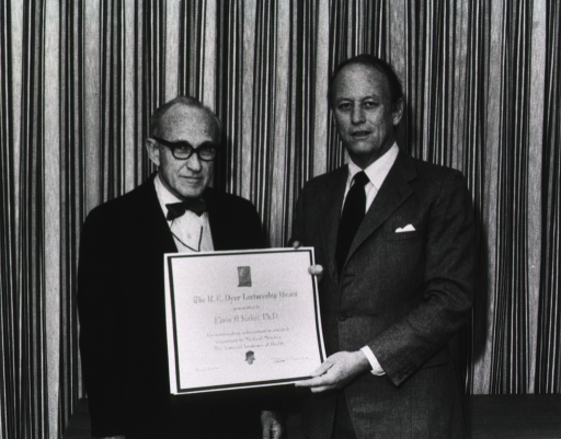<p>Dr. Donald S. Fredrickson, director of the National Institutes of Health, is holding the Dyer lecture award in front of Dr. Elvin Kabat, professor of human genetics and development at Columbia University.  They are standing in front of a stage curtain.</p>