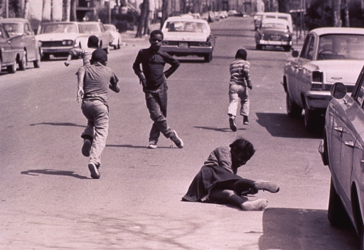 <p>Children are running in the street; a girl racing with several boys has fallen down.</p>