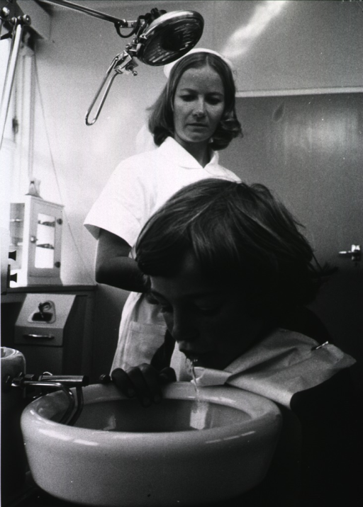 <p>Interior view of a dental office: a nurse observes as a young child rinses his mouth.</p>