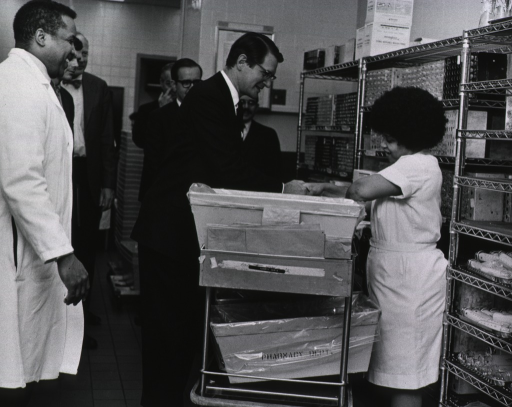 <p>An African American woman is standing behind a cart with bins and envelopes as she shakes Elliot Richardson's hand.  A group of men are standing behind Secretary Richardson.  Metal shelves are in the background.</p>