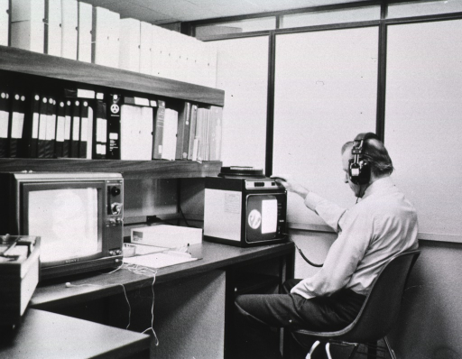 <p>Interior view: Patron with a headset on is sitting in front of a slide projector.  A video is playing next to him.  The shelves above the machinery house video cases and slide carousels.</p>