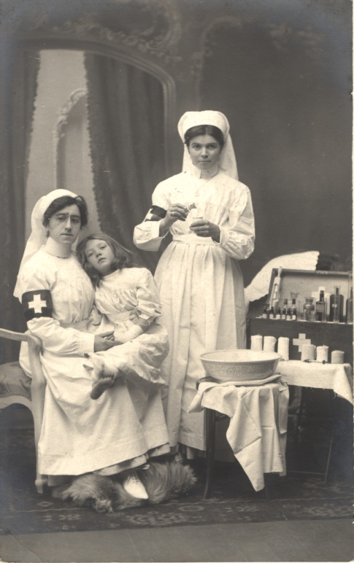 <p>Postcard featuring a black and white photograph of two nurses with a young girl. The girl is wearing white and has bandages on one of her feet and on one of her hands. She is sitting on the lap of one of the nurses, and she looks unhappy. The two nurses are dressed in white uniforms with a white cross on a black armband. The nurse holding the girl is wearing eyeglasses. The other nurse is standing up and pouring something from a bottle into a small cup. Nearby there is a stool with a cloth and basin on it and a small stand with a chest of medicines and some bandages. Handwritten note on verso states &quot;real photo - Belgium nurses, pre WW1.&quot;</p>
