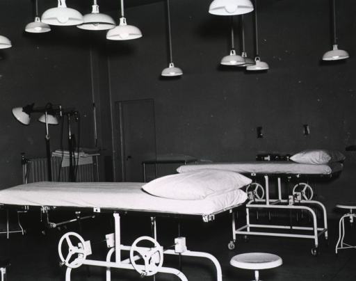 <p>Two operating tables are stationed in a high-ceilinged room.</p>