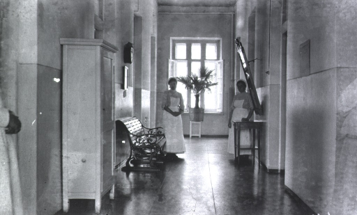 <p>Two nurses stand in the hallway of the Naval Hospital.</p>