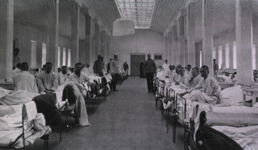 <p>Patients, medical personnel and a priest are in a ward in Kaufman No. 2 Red Cross Hospital.</p>