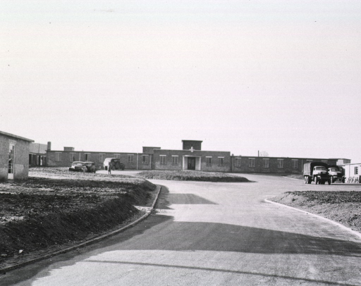 <p>View of the hospital complex as seen from the driveway.  Several vehicles are parked in the driveway. A serviceman can be seen walking in front of the building.</p>