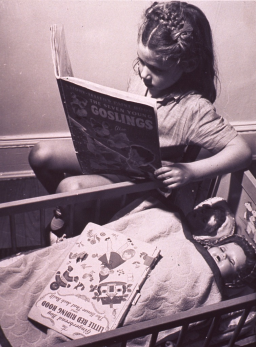 <p>A little girl is reading bedtime stories to her dolls.</p>