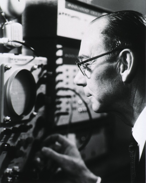 <p>Head and shoulders, half length, left profile; wearing glasses; turning knob on oscilloscope.</p>