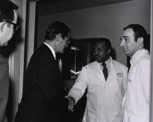 <p>Elliot Richardson shakes hands with the CC pharmacy dept. central sterile supply chief.</p>