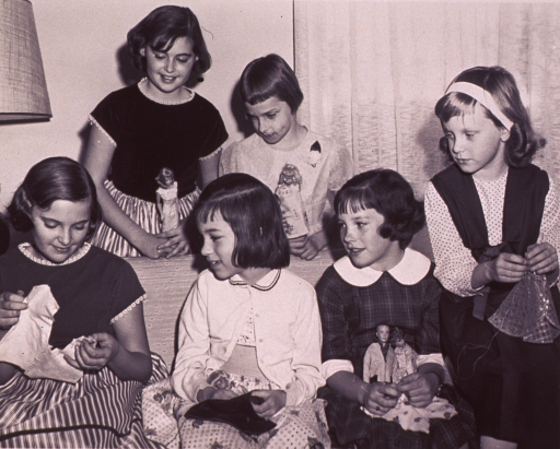 <p>Members of Barbie Fan Club Chapter No. 2000; a group of girls with their Barbie dolls and some clothing that they have made for the dolls.</p>
