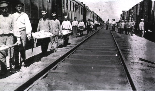 <p>Soldiers(?) carry empty litters at a hospital railroad station.</p>
