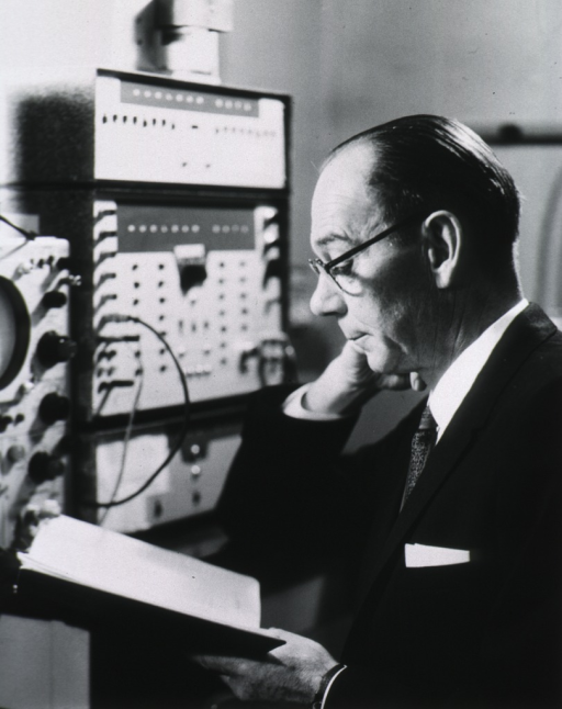 <p>Head and shoulders, left profile; wearing glasses; reading; hand to chin; oscilloscope in background.</p>