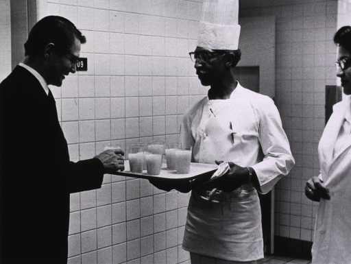 <p>CC Nutrition Chef Coleman Chandler serves juice to Elliot Richardson during his visit to NIH on March 16, 1971.</p>