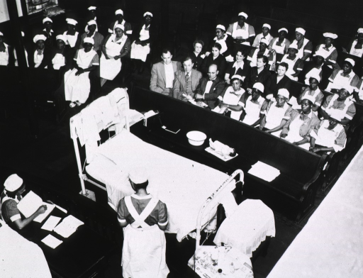 <p>Interior view of a church: several men and women sit with many African American women wearing nursing uniforms; a bed and a table are in the foreground; an instructor stands at the bed and another nurse sits at a table on the left; there is a doll on the front pew.</p>