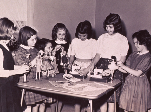 <p>Members of Barbie Fan Club Chapter No. 3000; a group of girls standing around a table with their Barbie dolls; they are making clothes for the dolls.</p>