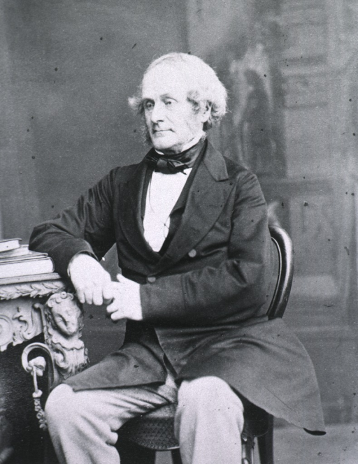 <p>Seated with arm resting on desk, left pose.</p>