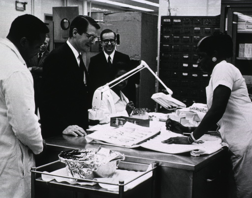 <p>An African American woman, standing behind a desk, explains wrapping procedures to Elliot Richardson.  The pharmacy dept. chief is standing to Secretary Richardson's right.</p>