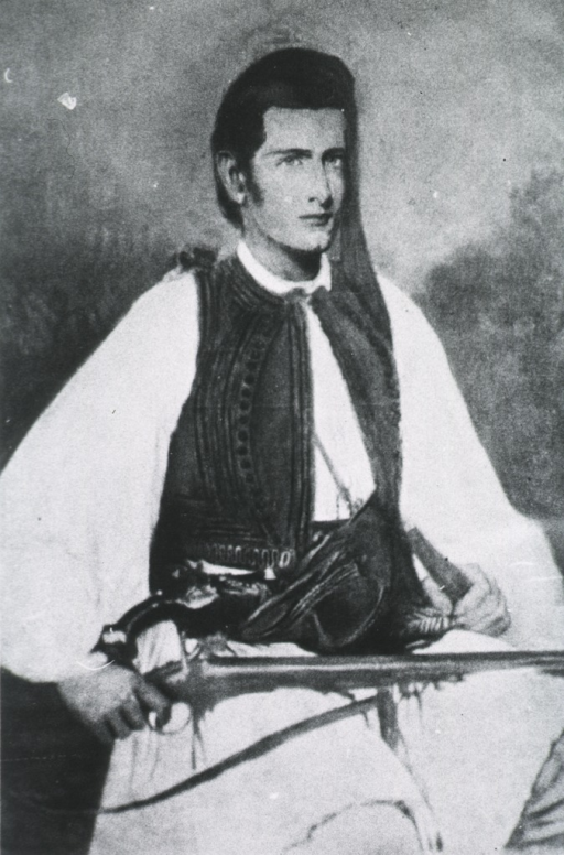 <p>In costume of a Greek soldier, holding gun.</p>