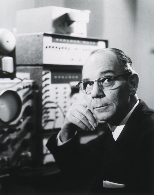 <p>Head and shoulders, left pose, full face; wearing glasses; hand to cheek; oscilloscope and other electronic apparatus in background.</p>