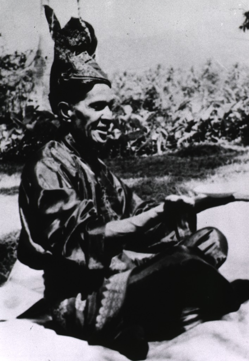 <p>A man is sitting on the ground, legs crossed, arms are extended in front of his body with his hands turned palms up holding a small dish.</p>