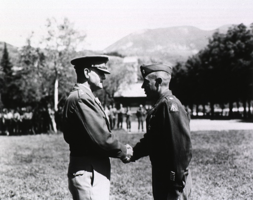 <p>Subect:  The two servicemen stand in profile shaking hands on a field.  In the background, a row of men stand and watch.  In the distance rise mountains.</p>