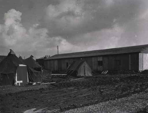 <p>Two tents stand next to a long, one-story building. A sign reading &quot;X-ray Department&quot; is posted in front of one of the tents.</p>