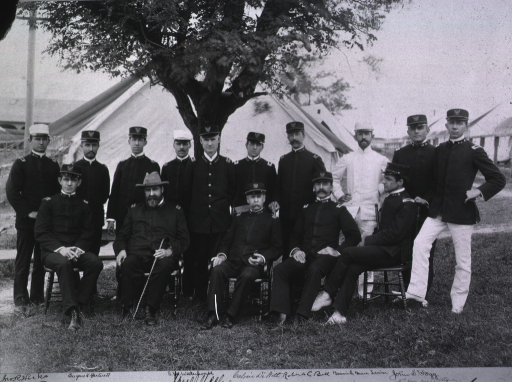 <p>A group of men sitting and standing under a tree; one in white uniform, others in dark uniforms; tent in the background.</p>