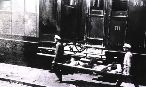 <p>A patient is carried on a litter by two soldiers(?) at a hospital train station.</p>