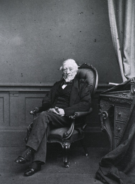 <p>Seated with hands in lap; left pose.</p>