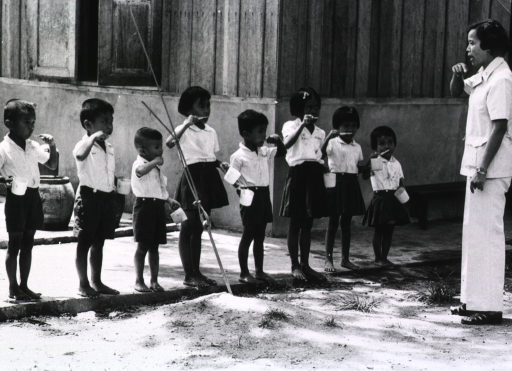 <p>Exterior view: a group of young children are being taught proper toothbrushing techniques.</p>