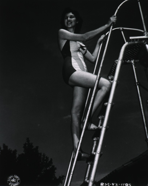 <p>Full length, full face; standing on steps; wearing swim suit.</p>