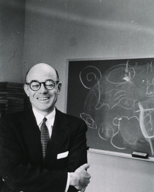 <p>Half-length, standing, full face, smiling; wearing glasses; blackboard in background.</p>