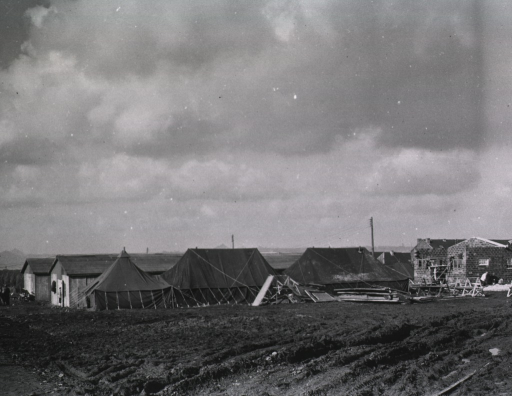 <p>A group of tents and partially-constructed buidlings on a grassless plain.</p>