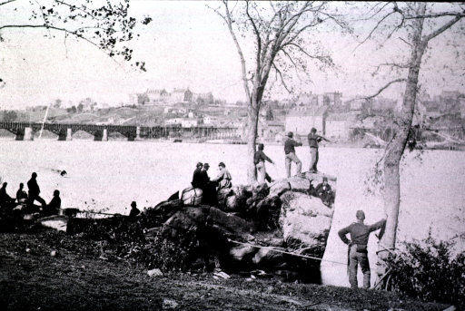 <p>A group of soldiers is positioned on the Virginia side of the Potomac River, near the Georgetown Aqueduct and Georgetown College.</p>