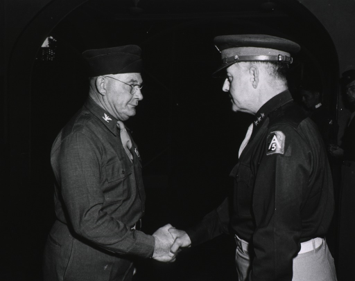 <p>Two servicemen stand in profile shaking hands in a room.  Several other servicemen are seen standing in the background.</p>