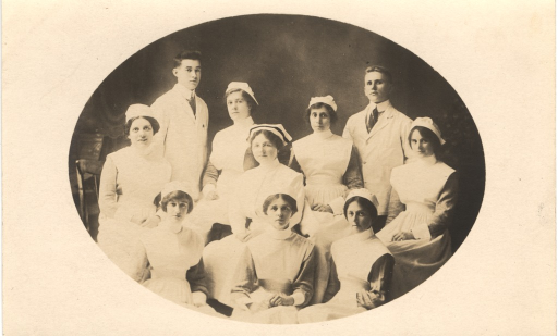 <p>Postcard featuring a black and white photograph of a medical staff consisting of eight women and two men. They are all dressed mostly in white. The men are standing and the women are sitting. Both of the men are wearing neckties. The women are dressed as nurses and are wearing white caps. One nurse is wearing glasses and has a dark stripe on her cap.</p>