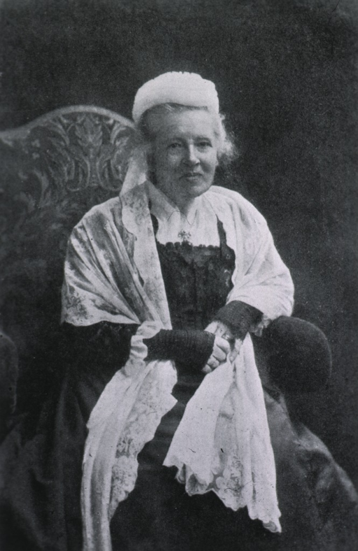 <p>Seated, front pose; wearing cap and white lace shawl.</p>