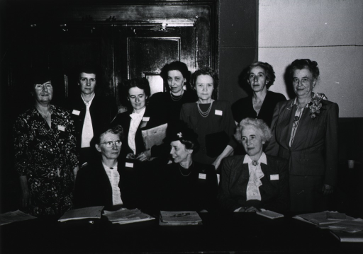 <p>View of several women, gathered around a table, who served on the board.</p>